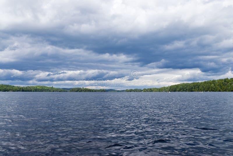 在p地方上的天空的阿尔根金族独木舟黑暗的湖 库存图片