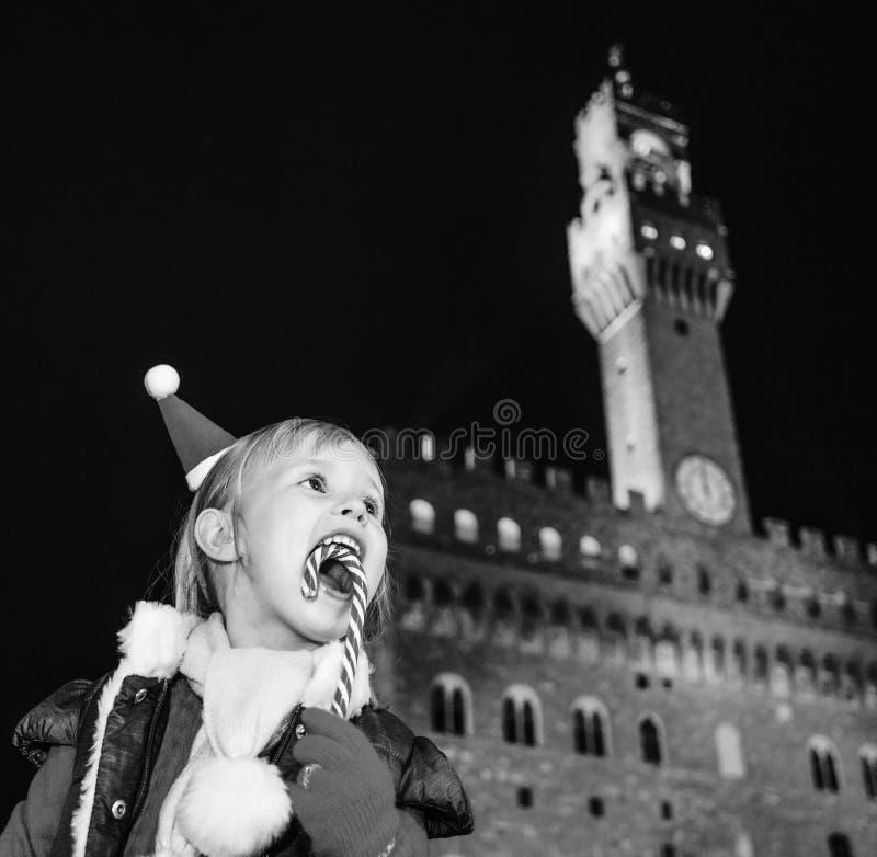 在Palazzo Vecchio前面的微笑的女孩吃圣诞节藤茎的 免版税库存图片
