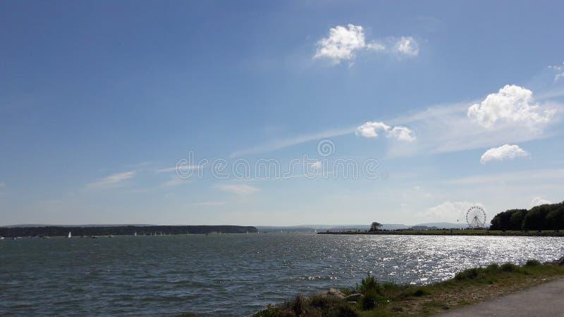 在Parkstone海湾的晴天与重要人物背景,多西特,英国 免版税库存照片