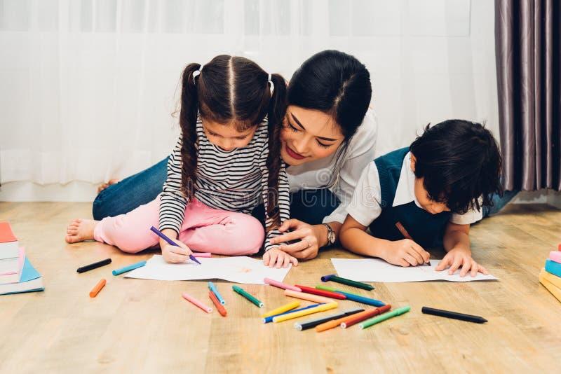在peper老师教育的愉快的儿童孩子男孩和女孩儿子幼儿园图画与美丽的母亲 库存照片