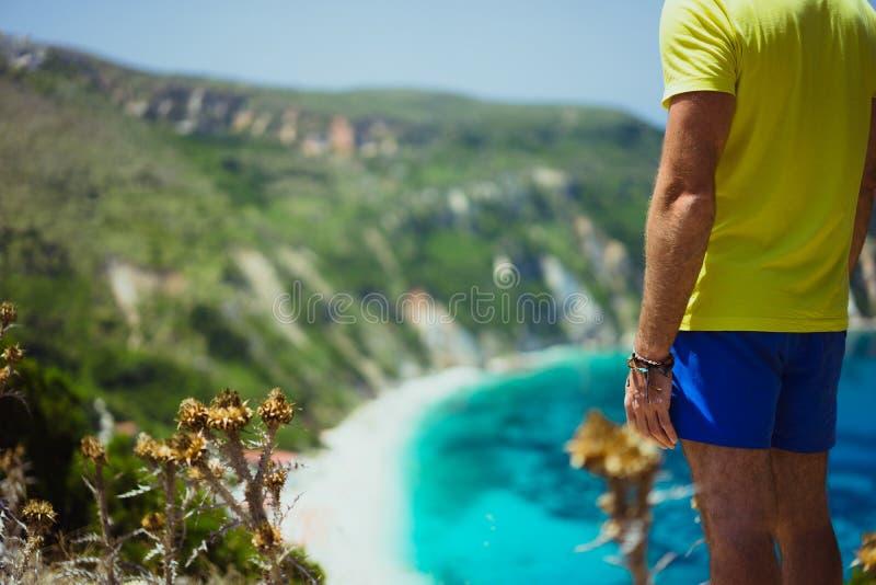 在Petani海滩享受鲜绿色天蓝色的海湾盐水湖的美丽如画的全景Kefalonia的男性旅游佩带的短裤 免版税库存图片