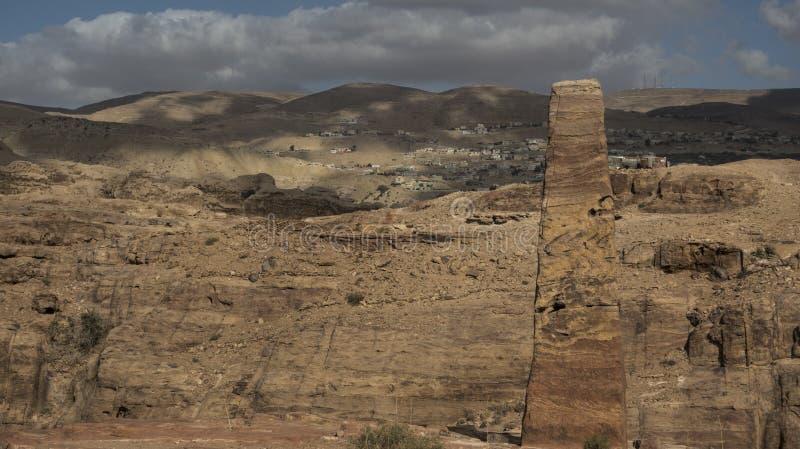 在Petra考古学站点的戏弄与Uum Sayhoun村庄的方尖碑和云彩  库存图片