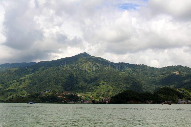 在Phewa湖和小山在博克拉,一个普遍的游人附近的小船 库存图片