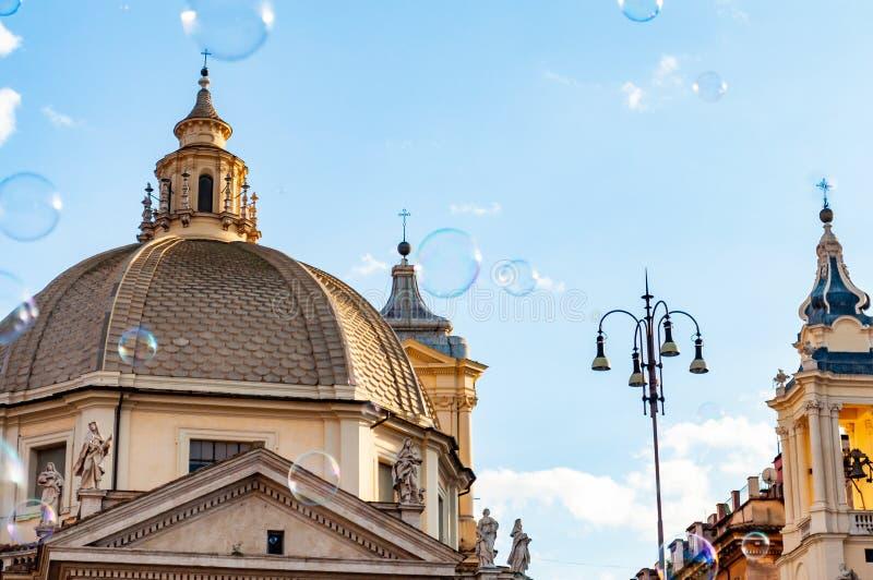 在Piazza del Popolo,人正方形的肥皂泡飞行在罗马由象圣玛丽亚的古老教会围拢了在Montesanto与 库存图片