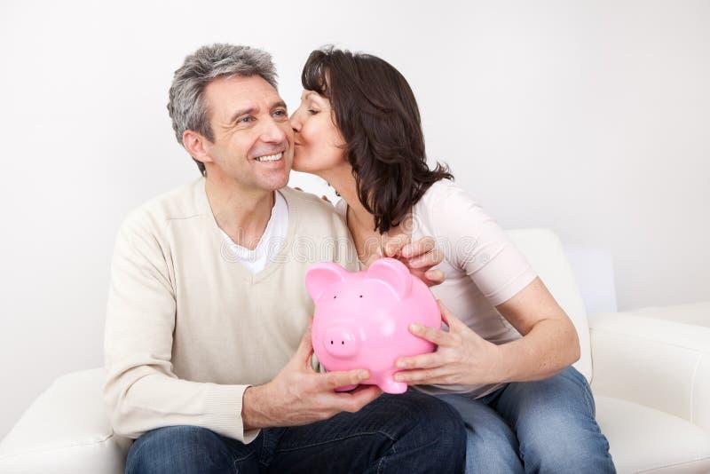 在piggybank的成熟夫妇节省额货币 免版税库存图片