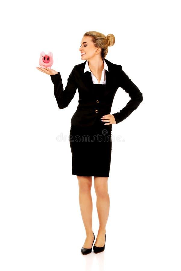 在piggybank的年轻女实业家挽救金钱 库存照片