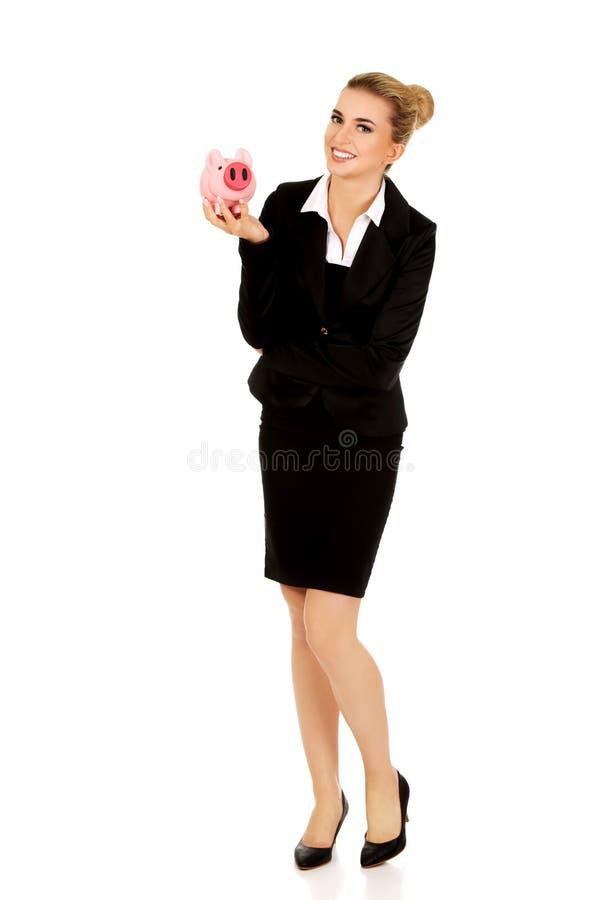 在piggybank的年轻女实业家挽救金钱 免版税库存照片