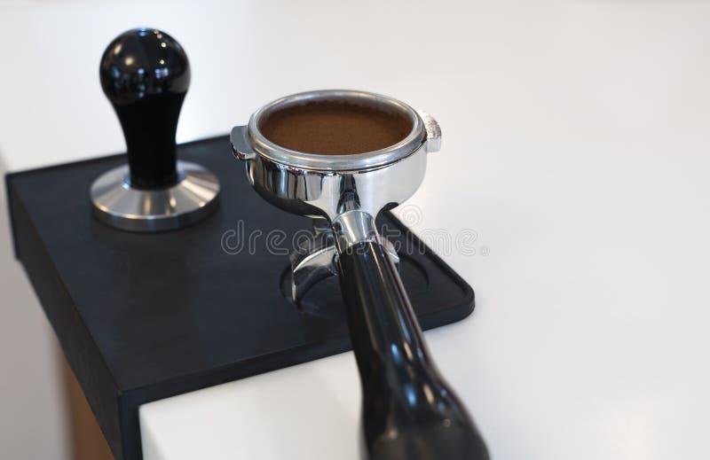 在portafilter的被砸紧的和变紧密的咖啡渣 免版税库存图片