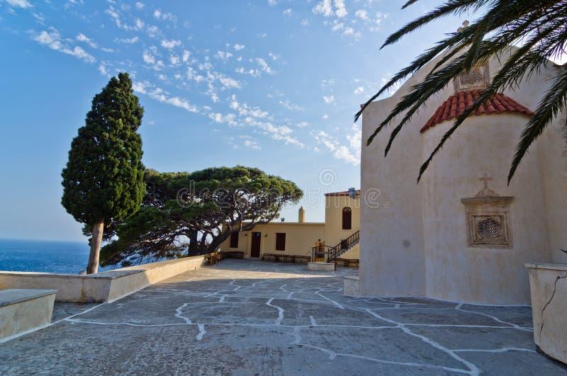 在Preveli修道院,克利特海岛里面的教堂、棕榈和柏树  免版税库存照片