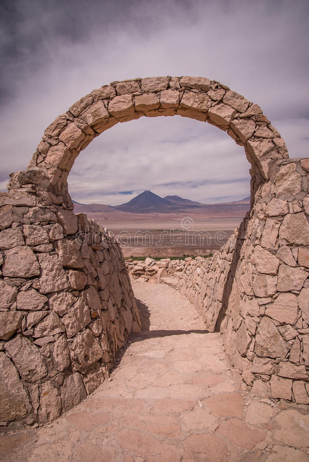 在Pukara de Quitor -阿塔卡马沙漠的印加人堡垒的石门有在利坎卡武尔火山火山的看法在安地斯,圣佩德罗火山de Atacam 库存照片