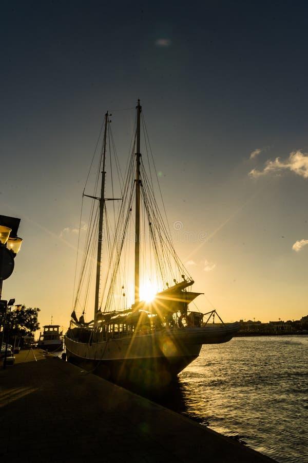 在Punda的日落有在太阳的小船的 免版税图库摄影