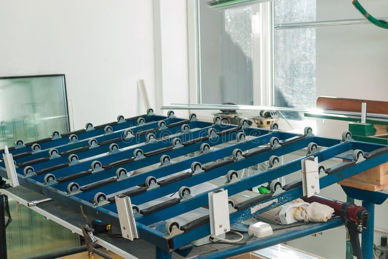 在PVC窗口工厂的自动玻璃切割桌 库存照片