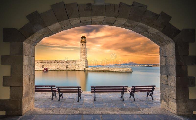 在Rethimno老港口的埃及灯塔通过一个被成拱形的门,克利特的框架 库存图片