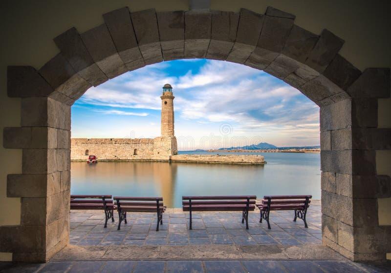 在Rethimno老港口的埃及灯塔通过一个被成拱形的门,克利特的框架 免版税库存照片