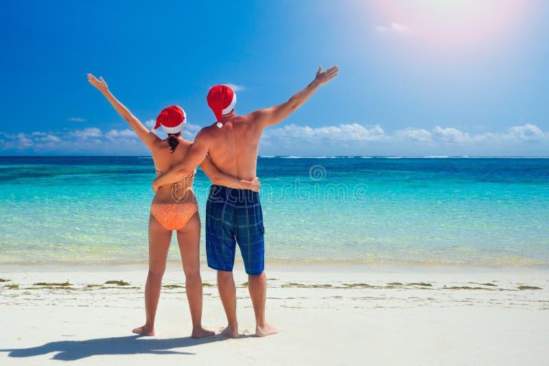 在santa& x27的夫妇; 在一个热带海滩的s帽子 图库摄影