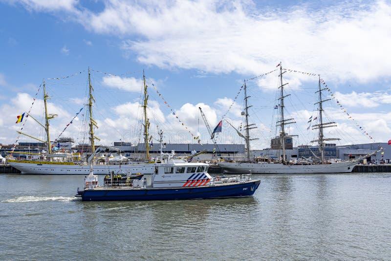在Scheveninge的风帆期间一艘现代水警艇通过Tallships米尔恰和Shabab阿曼II,在斯海弗宁恩港口  免版税库存图片