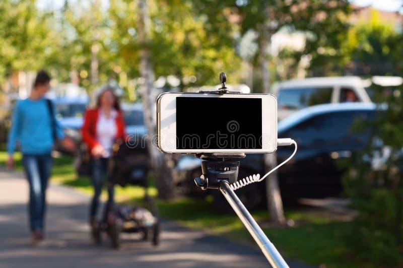 在selfie棍子的白色电话 库存图片
