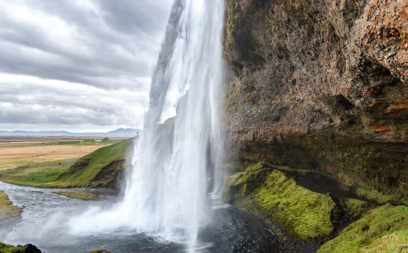 在Seljalandsfoss瀑布,南冰岛的仔细的审视 免版税库存照片