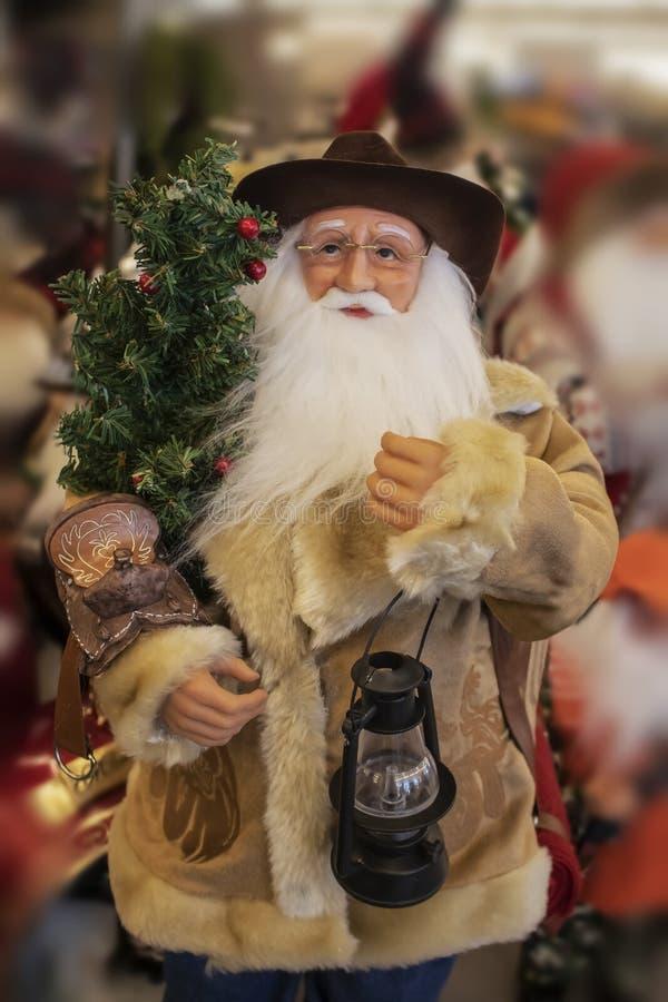 在shearling外套有马鞍和灯笼的和圣诞树-选择聚焦的牛仔圣诞老人项目-被弄脏的背景 库存照片
