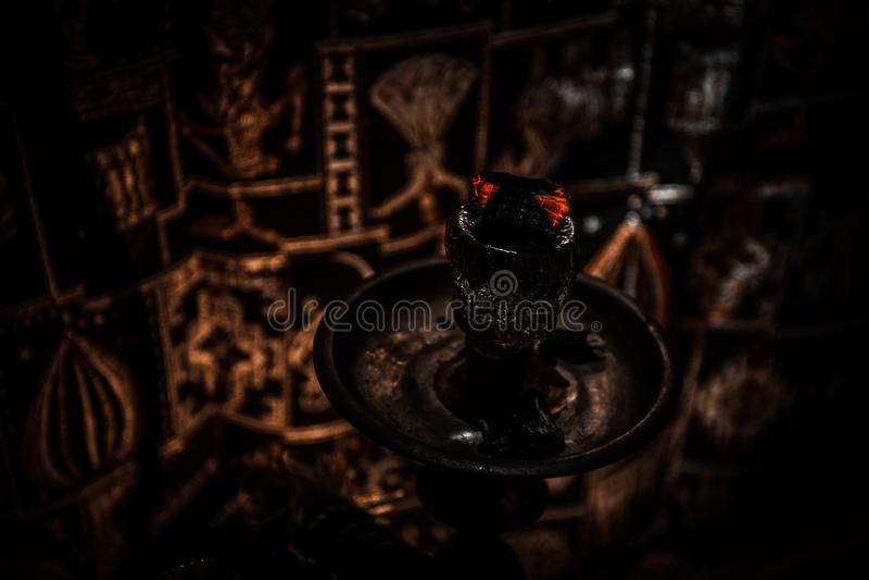 在shisha碗的水烟筒热的煤炭在黑暗的有雾的背景 时髦的东方shisha 图库摄影