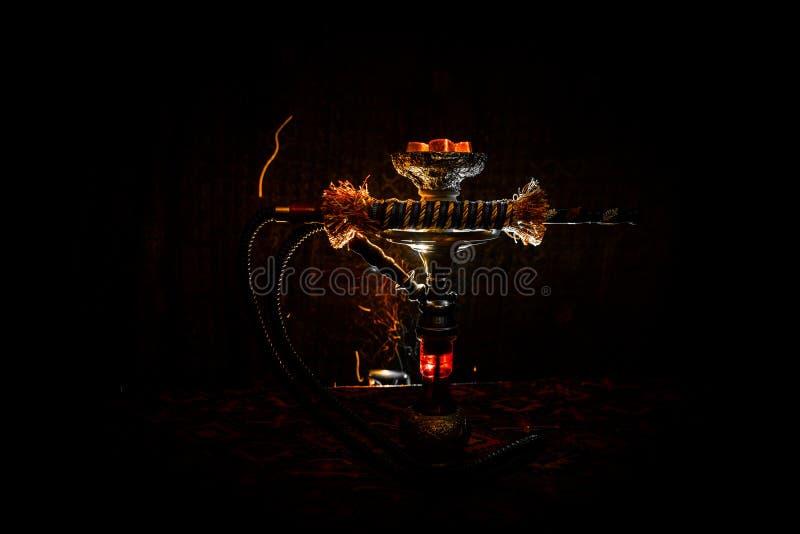 在shisha碗的水烟筒热的煤炭在黑暗的有雾的背景 时髦的东方shisha 库存照片