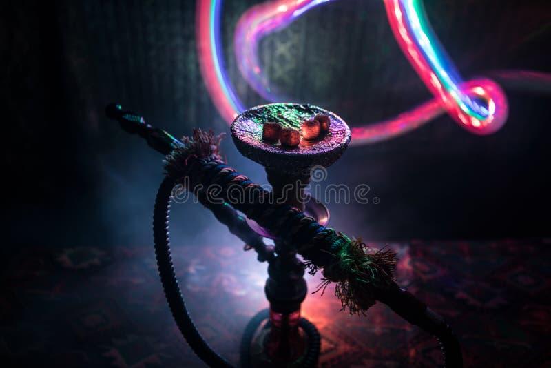 在shisha碗的水烟筒热的煤炭在黑暗的有雾的背景 时髦的东方shisha 库存图片