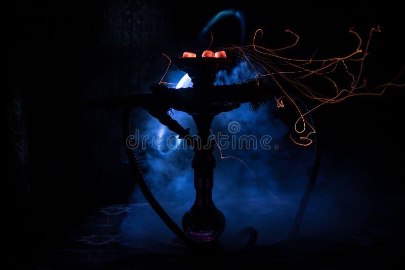 在shisha碗的水烟筒热的煤炭在黑暗的有雾的背景 时髦的东方shisha 免版税库存照片