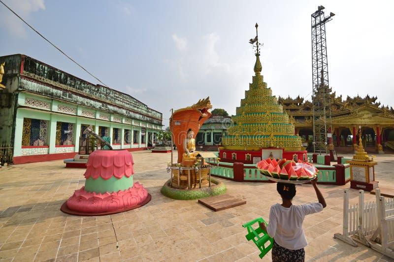 在Shwemawdaw塔的寺庙有运载在头的供营商的被切的西瓜 免版税库存图片