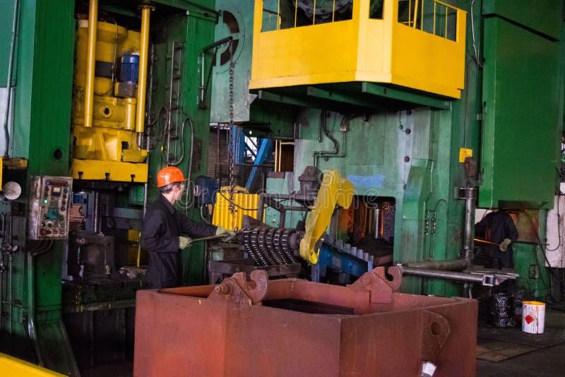 在smeltery的热的铁由工作者举行了 高精度热的锻件产品,由热的伪造的过程的汽车部分生产,自动 库存图片
