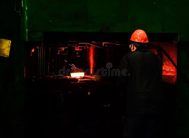 在smeltery的热的铁由工作者举行了 免版税库存图片