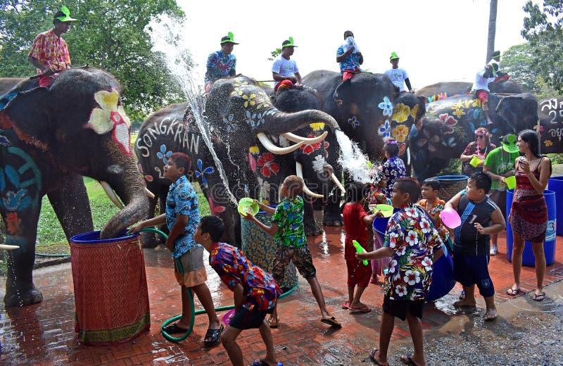 在Songkran期间,大象演奏与孩子的水争斗 免版税库存图片