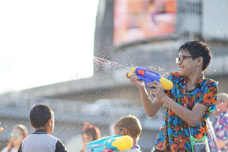 在Songkran期间,孩子演奏水 库存图片