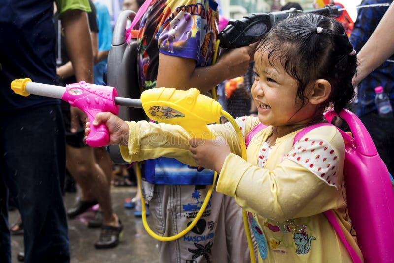 在Songkran节日的小的亚洲女孩射击水枪在禁令 免版税库存图片