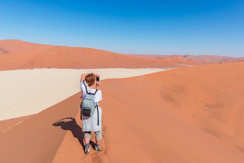 在Sossusvlei,纳米比亚的旅游采取的照片 风景沙丘,纳米比亚沙漠, Namib Naukluft国家公园,在Af的旅行冒险 免版税图库摄影