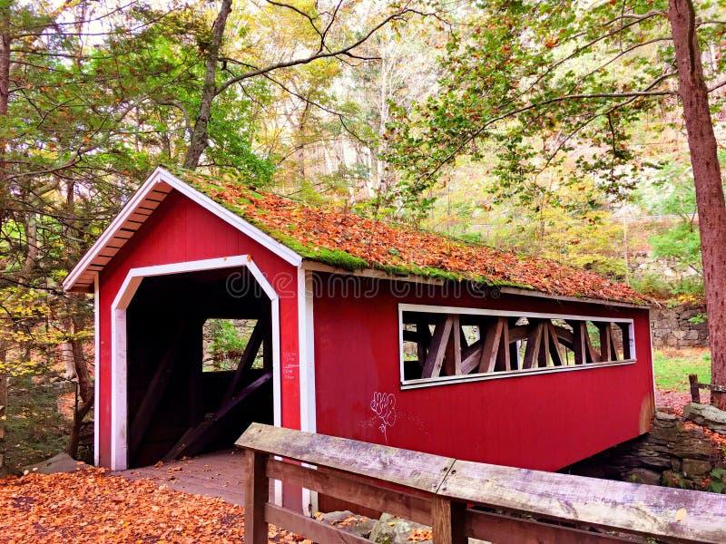 在Southford里面的一个红色被盖的木桥落国家公园 库存照片