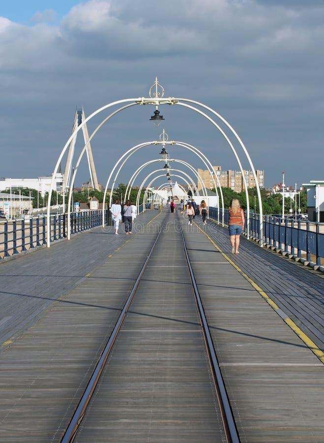 在southport默西赛德郡的历史的码头与走向镇和吊桥和大厦可看见的beh的人 免版税图库摄影
