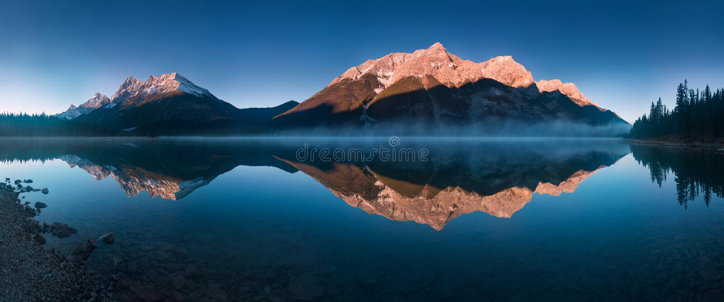 在Spray湖水库的平静的日出是一个水库在阿尔伯塔,加拿大 Spray湖 免版税图库摄影