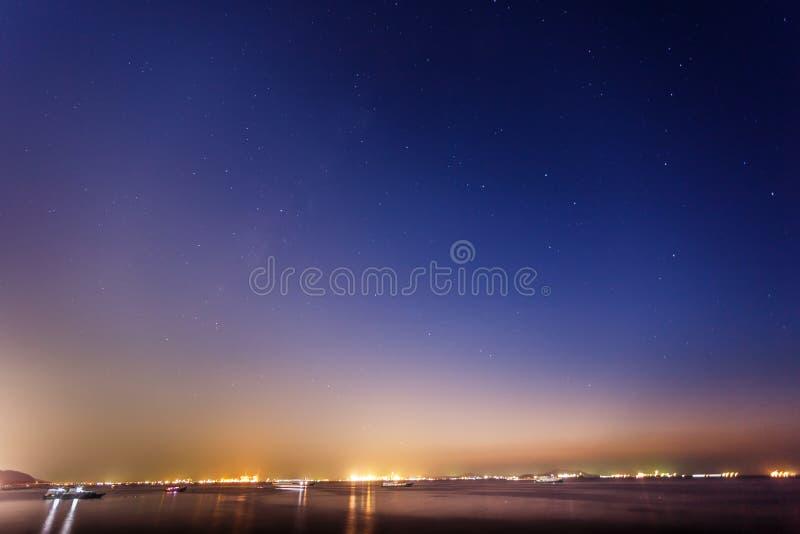 在Sriracha海岸泰国上的银河在暮色日落,与丰足星,夜景长的曝光技术的天空蔚蓝期间 免版税库存照片