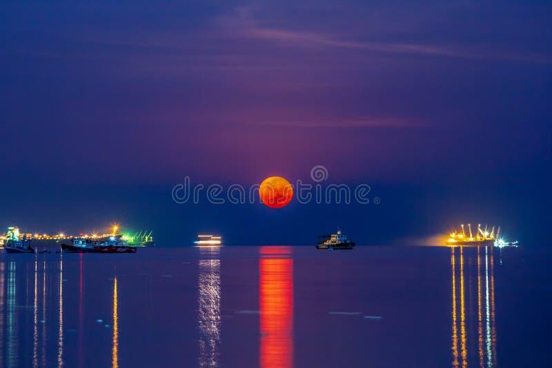 在Sriracha港口的超级血液月亮有船海水表面上的货箱船的 夜景射击 免版税库存照片