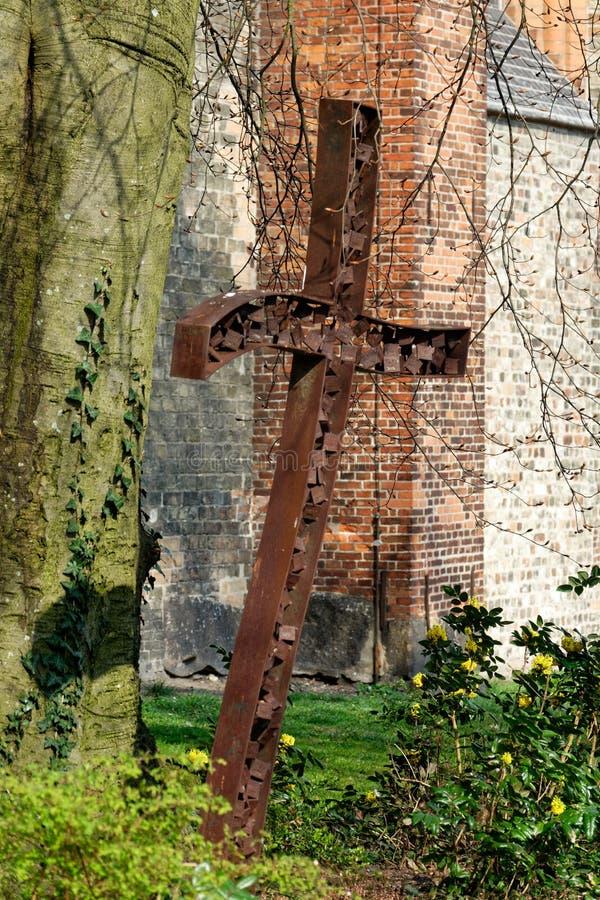 在StNikolaikirche前面的金属十字架在Flensburg/石勒苏益格霍尔斯坦德国 库存图片