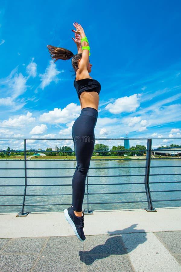 在strainght和肌肉修造跳跃的outd的少妇锻炼 免版税库存图片