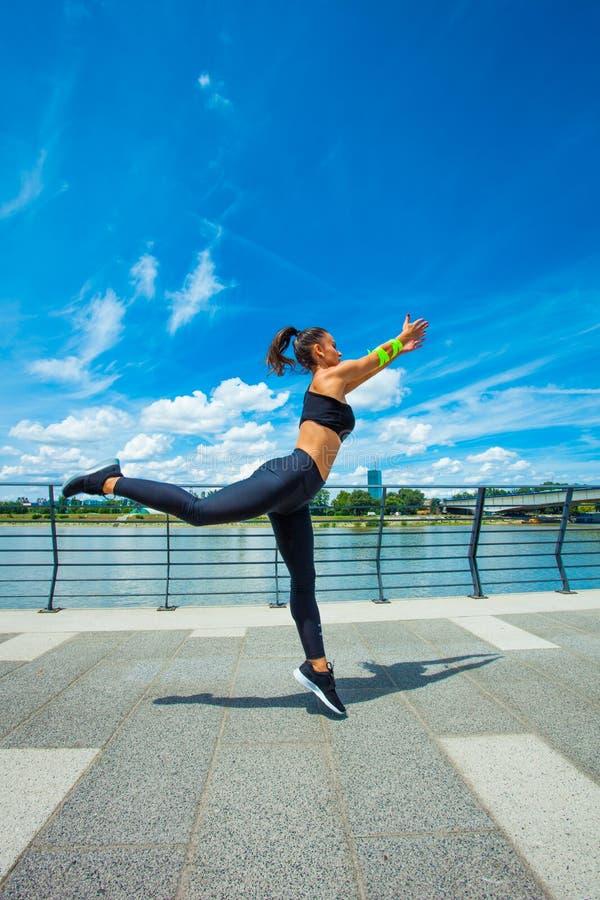在strainght和肌肉修造跳跃的outd的少妇锻炼 库存图片