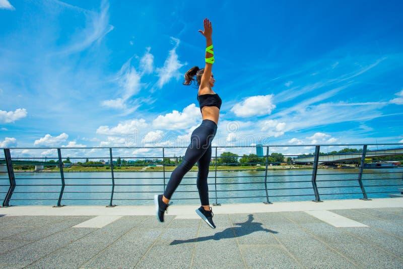 在strainght和肌肉修造跳跃的outd的少妇锻炼 图库摄影