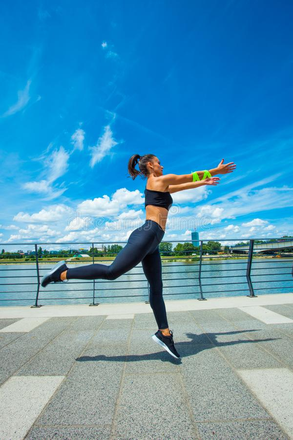 在strainght和肌肉修造跳跃的outd的少妇锻炼 免版税图库摄影