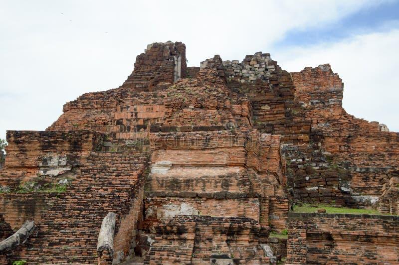 在stupa前面的老粉碎的长满的砖墙在历史公园泰国 免版税库存照片