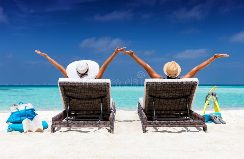 在sunbeds的愉快的夫妇在一个热带海滩 库存照片