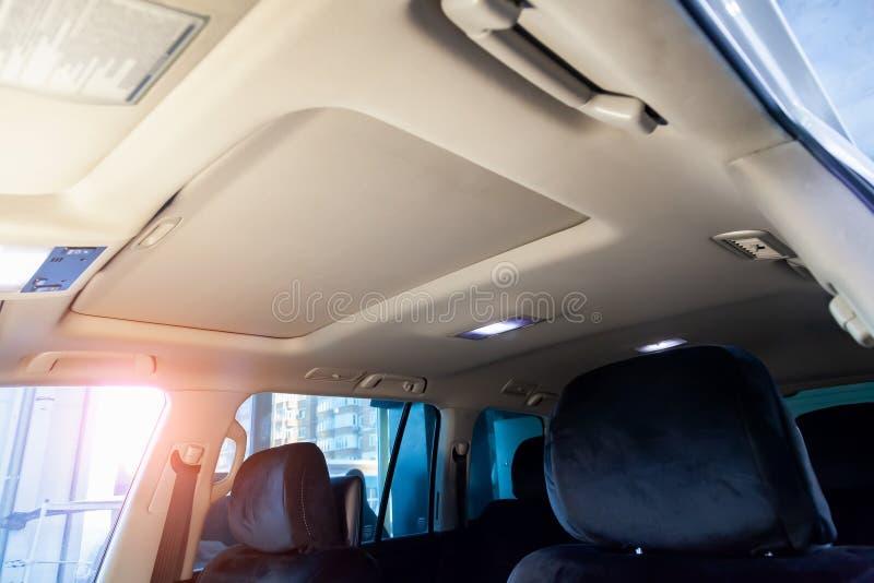 在SUV的客舱的轻的米黄天花板在干洗以后的和季节性检查在修理和维护的车间 库存图片