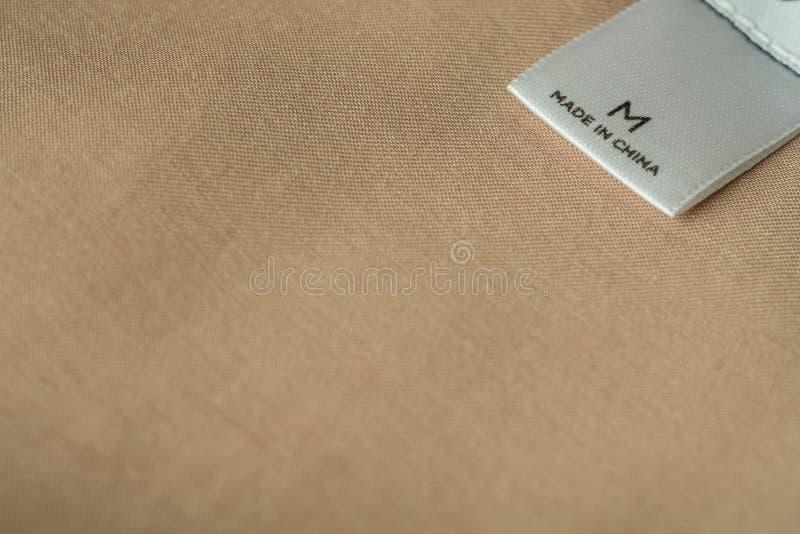 在t在上写字的中国制造衣裳标签宏观射击的关闭 免版税图库摄影