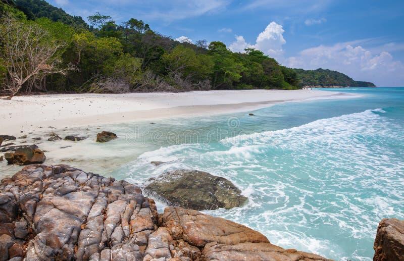 在Tacai海岛的美丽的石海滩和水飞溅 免版税图库摄影
