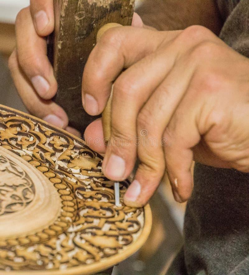 在Tas的Chorsu义卖市场附近供以人员凿子木刻在车间 免版税库存照片